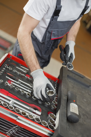 car repair shop: High angle view of male mechanic arranging tools in drawer at car repair shop