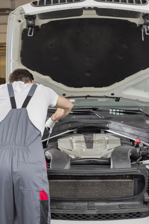 automobile repair shop: Rear view of male engineer repairing car in automobile repair shop