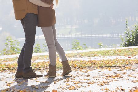 low section: Low section of couple standing in park during autumn