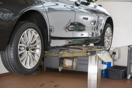 car hoist: Car on hoist at repair shop