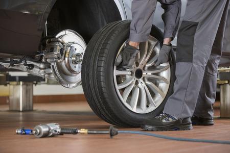 tire repair shop: Low section of male mechanic repairing cars tire in repair shop LANG_EVOIMAGES