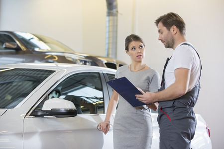 automobile repair shop: Repairman holding clipboard while conversing with female customer in automobile repair shop