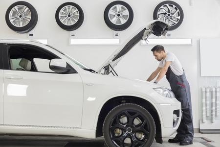 mecanico: Vista lateral de cuerpo entero de examinar motor del coche mec�nico de varones en taller de reparaciones