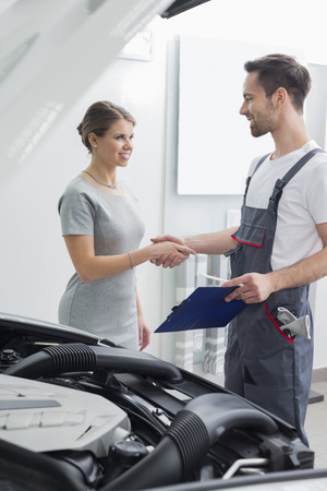 maintaining: Young repair worker shaking hands with customer in car workshop LANG_EVOIMAGES