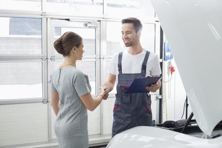 car repair shop: Smiling maintenance engineer shaking hands with female customer in car repair shop