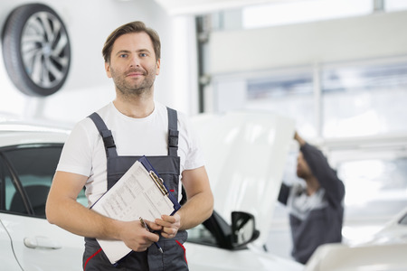 car repair shop: Portrait of confident male maintenance engineer with clipboard in car repair shop