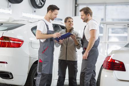 car repair shop: Automobile mechanics discussing over clipboard in car repair shop
