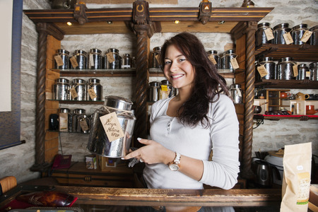 Portrait of smiling salesperson displaying tea container in store Stock Photo