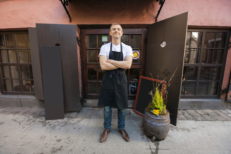 business products: Portrait of confident male salesperson standing arms crossed outside coffee store