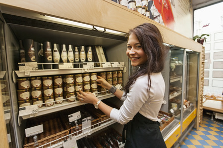Portrait of smiling saleswoman arranding products in supermarket Stock Photo