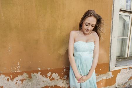 tube top: Shy teenage girl in tube dress standing against wall