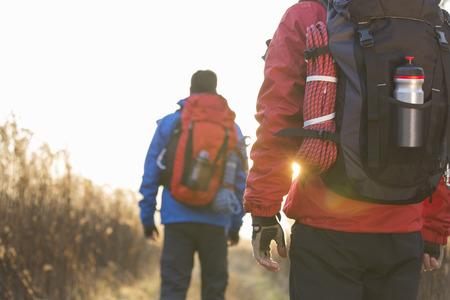 フィールドで歩いている男性バックパッカーの背面図 写真素材