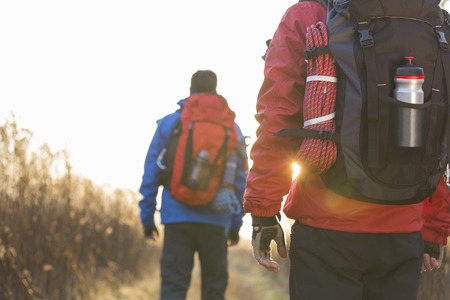 warm clothes: Rear view of male backpackers walking in field