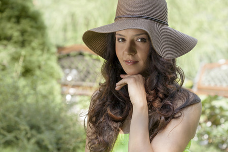 brim: Portrait of beautiful young woman wearing sunhat in park