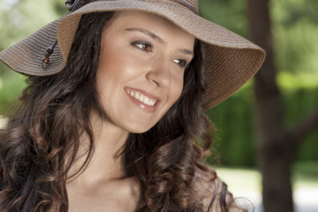sunhat: Smiling young woman in sunhat looking away in park