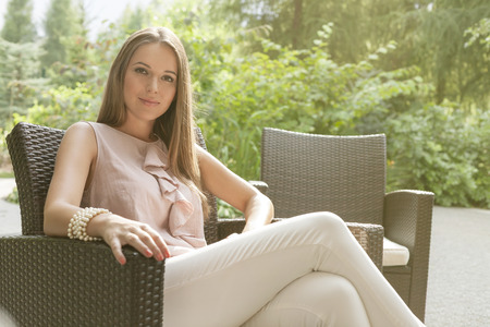 easy chair: Portrait of beautiful young woman relaxing on chair in park LANG_EVOIMAGES