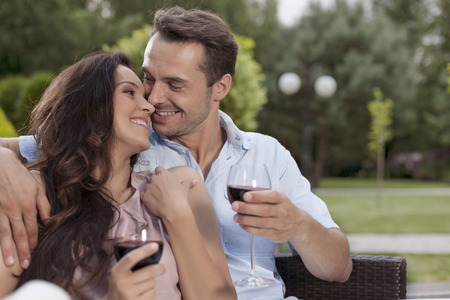 easy chair: Affectionate young couple having red wine in park LANG_EVOIMAGES