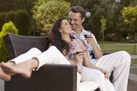 easy chair: Romantic young holding wine glasses on easy chair in park