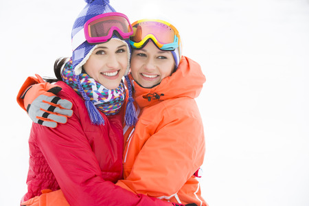 warm clothing: Portrait of happy young women in warm clothing embracing outdoors
