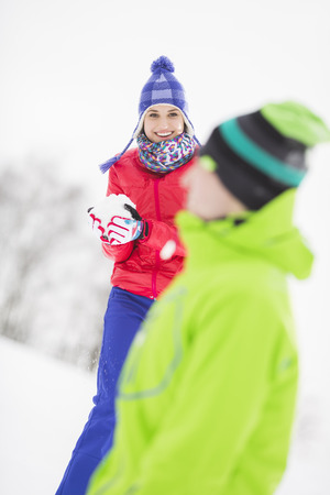 people: Smiling young woman having snowball fight with male friend