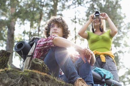 looking away from camera: Young female hiker photographing through digital camera while man looking away in forest