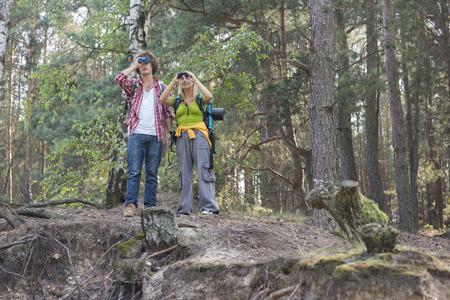 using binoculars: Hiking couple using binoculars in forest