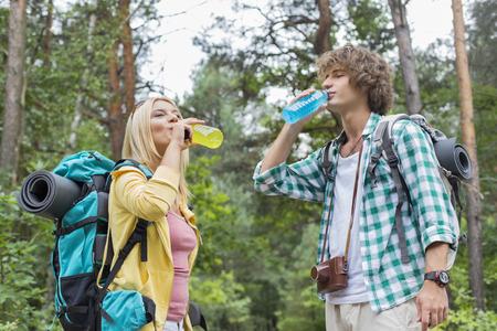 Jóvenes bebidas energéticas pareja beber senderismo en el bosque