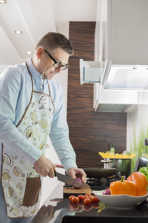 cutting vegetables: Mid-adult man cutting vegetables at kitchen counter