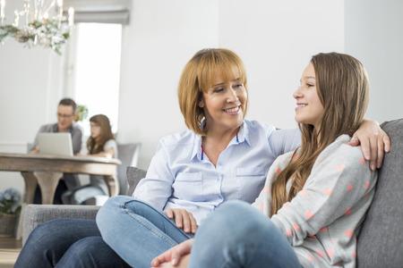 madre e hija adolescente: madre cariñosa e hija sentada en el sofá con la familia en segundo plano LANG_EVOIMAGES