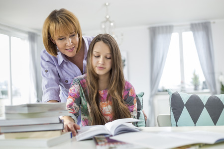 madre soltera: Madre ayudando a su hija en hacer los deberes en la mesa