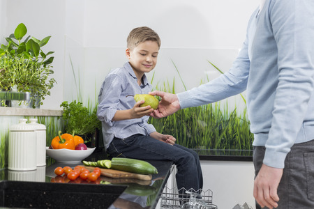 midsection: Midsection of father giving pear to son in kitchen