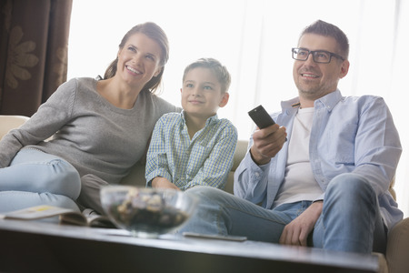 woman watching tv: Boy viendo la televisi�n con los padres en la sala de estar