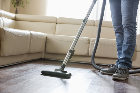 low section: Low section of man cleaning hardwood floor with vacuum cleaner