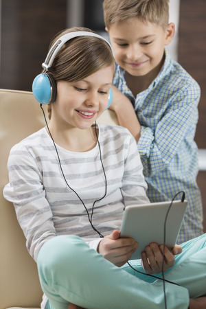 family: Cute girl listening music on digital tablet while brother standing behind her at home