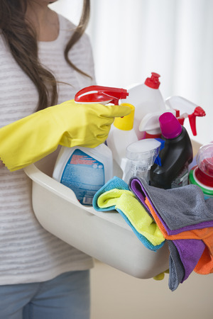 cleaning supplies: Midsection of woman carrying basket of cleaning supplies at home