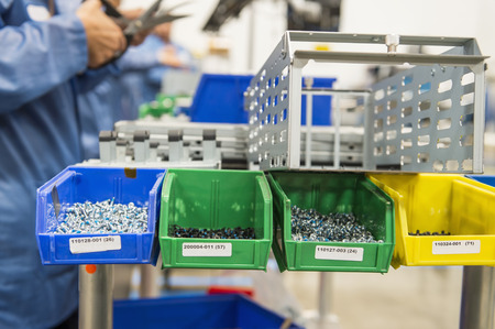 electronics industry: Variety of screws in tray with engineers working at electronics industry