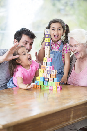 multi family house: Happy multi generation family with arranged building blocks at table in house LANG_EVOIMAGES