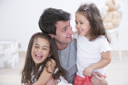 quality home: Happy father with daughters spending quality time together at home