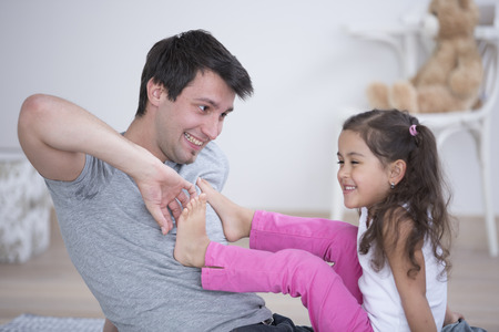 tickling: Father tickling daughters foot at home LANG_EVOIMAGES
