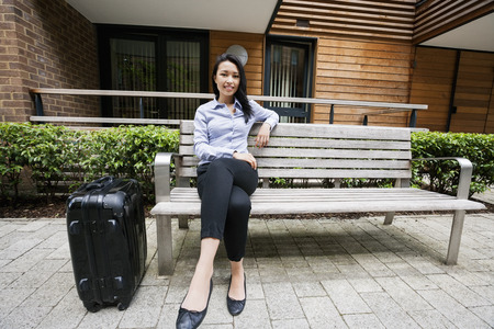 Full length of confident businesswoman sitting on bench by luggage against building Stock Photo