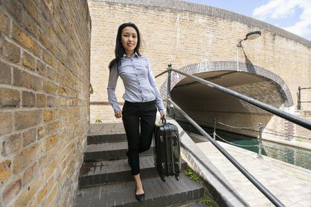 bajando escaleras: Retrato de cuerpo entero de la joven empresaria con equipaje caminando por las escaleras