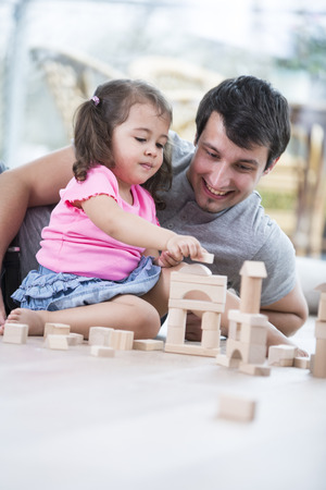 blocks: Little girl and father playing with wooden building blocks on floor