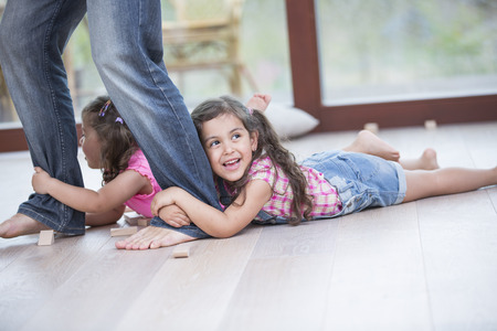 elementary age girl: Low section of father dragging girls on hardwood floor