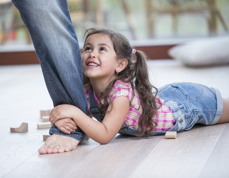 low section: Low section of father dragging girl on hardwood floor