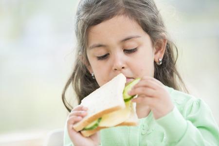 comiendo pan: Linda chica comiendo s�ndwich en casa LANG_EVOIMAGES