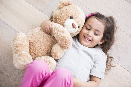 Girl with teddy bear lying on wooden floor at home