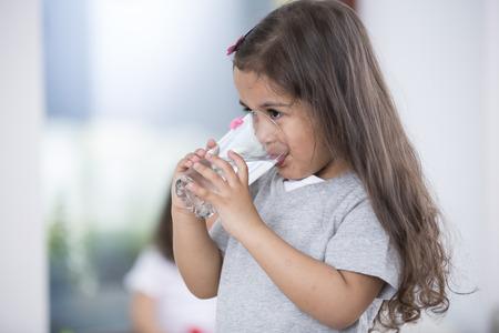vasos de agua: Ni�a vaso linda de agua en el hogar
