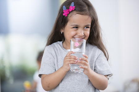 집에서 물 한 잔을 들고 웃는 귀여운 소녀