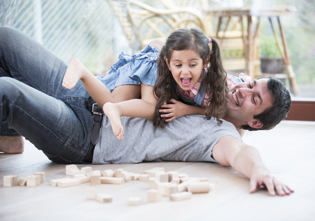 single parent family: Playful daughters on top of father at home