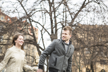 czech women: Smiling young man and woman holding hands and walking outdoors LANG_EVOIMAGES